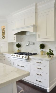 White kitchen cabinetry, marble counters and backsplash, range hood | Dearborn Cabinetry