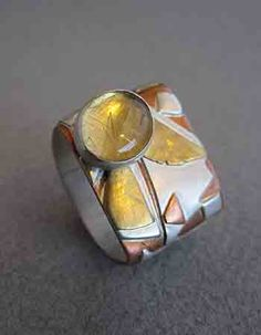 "Flying Geometry, Patricia Kidwell'Lown, Ring, sterling silver, copper, and 24K gold, rutilated quartz, 3/4"" wide"