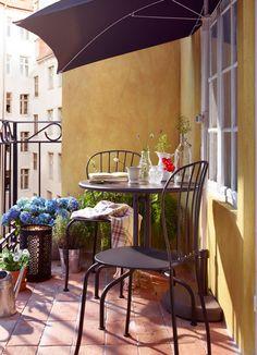 Aurinkoinen parveke, jossa harmaat pöytä ja tuolit sekä puoliympyrän muotoinen auringonvarjo.