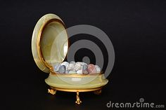 Vintage jewelry box made of onyx and golden metal filled with little stones on a black background