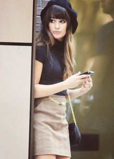 Lea Michele as Rachel berry - Tan skirt, nude legs, black shirt, beret and purse and her shoes or boots are probably black as well.