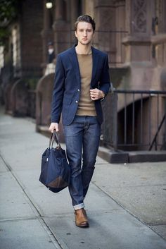 Something as simple as teaming a dark blue blazer jacket with navy jeans can potentially set you apart from the crowd. Add brown leather chelsea boots to your look for an instant style upgrade.   Shop this look on Lookastic: https://lookastic.com/men/looks/blazer-crew-neck-sweater-jeans/18777   — Tan Crew-neck Sweater  — Navy Blazer  — Navy Jeans  — Navy Canvas Tote Bag  — Brown Leather Chelsea Boots
