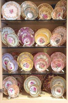 Dainty tea cup, saucer and tea plate display on glass shelves