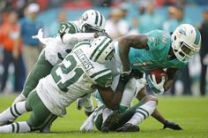 Miami Dolphins' Jarvis Landry, right, is tackled by New York Jets' Marcus Gilchrist during the NFL football game between the New York Jets and the Miami Dolphins and at Wembley stadium in London, Sunday, Oct. 4, 2015. (AP Photo/Matt Dunham)