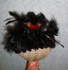 Black fuzzy waffle hat with Ostrich puff and red heart with wings embellishment.