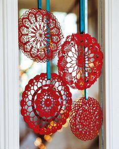 Decorazione di Natale: centrini inamidati e colorati di rosso da appendere alle finestre.