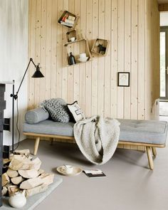 Wood wall paneling helps create a cozy, Nordic style fireside nook for this living room daybed.