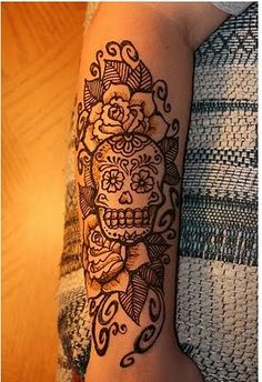 sugar skull and flowers arm tattoo