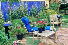 A simple backyard patio garden in Denver is transformed into an exotic scene by painting the enclosing wall a cobalt blue and adding some complimentary blue colored garden ornaments and accents. Columns of multihued hollyhocks complete the cozy scene.