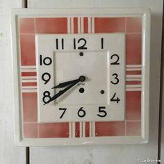 Horloge vintage en céramique blanche. Décors graphiques rouge. Aiguilles en tôle, noires. Fonctionne avec une pile 1,5 vlt.