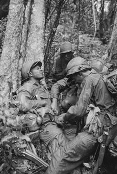 An American soldier is assisted by fellow troopers after being injured when his platoon made contact with Vietcong forces.