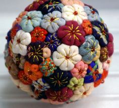 "Suffolk puffs stitched with gold to form flowers and attached to ""ball"" [pre-made felt or a polystyrene ball?]  Could be used as a pincushion."