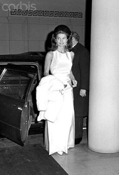 Jackie Kennedy with white fur coat Jacqueline Kennedy arriving to a formal function in a sleeveless evening gown and white gloves with a white fur coat over her arm. Date Photographed:September 27, 1966.❤♚❤ http://en.wikipedia.org/wiki/Jacqueline_Kennedy_Onassis