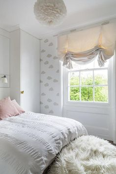 Beautifully designed pink and white girl's bedroom boasts gray clouds wallpaper framing a window covered with a cream shade positioned facing a white sheepskin bean bag placed in front of a bed dressed in a white ruched duvet topped with pink pillows lit by a sconce mounted beside a white cabinet fitted with a butterfly handle lit by a white feather chandelier.