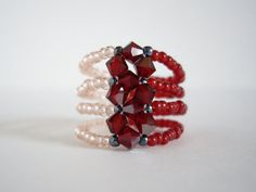This is an elegant peyote ring. I have used Japanese seed beads in drakest red, gunmetal and rosaline. I have also used Swarovski Elements Xilion