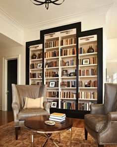 This stately bookcase is befitting the award-winning residence of the chancellor of North Carolina State University. Designed by Design Lines, Ltd. and built by Rufty Homes, it was constructed as four boxes that were then set flush in-wall. We especially like the faceplate overlay with the black lacquer finish that serves to frame the bookcase. Note how it was also used on the baseboard where the cabinets are set, anchoring it to the room.