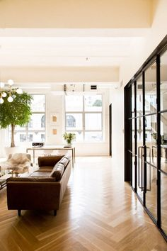 Bright industrial space with wood floors, large windows and a vintage leather sofa