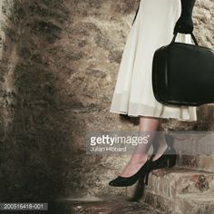 Stock Photo : Woman in white dress walking down stone steps, side view, low section
