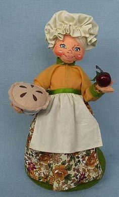 Annalee Doll Description: Open eyes, closed mouth smile, ivory hat and apron, mustard colored shirt, leaf print long shirt, holds pie in one hand and an apple in the other. Companion is 351912