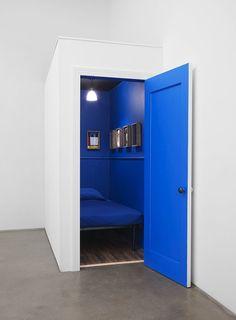 Peinture bleu semi-lustré sur les murs et l'intérieur de la porte de la petite pièce en contraste avec les murs blanc mat.