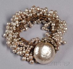 Vintage Imitation Baroque Pearl Bracelet, Miriam Haskell, designed as a fringe of imitation baroque pearls on braided gilded metal curb links, the clasp designed as a large imitation mabe pearl with imitation seed pearl and roses montees floral motifs, lg. 6 1/2 in., signed.