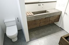 floating concrete/wood vanity supported by stubwall