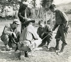 Two CBI soldiers discuss WWII operation in jungle clearing with village headsman and Kachin Ranger (with stick). Photographer Leipnitz