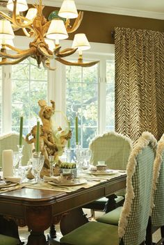 Brown walls, brown zebra curtains, faux antler chandelier. Love the green and white chairs, heavy brush fringe.
