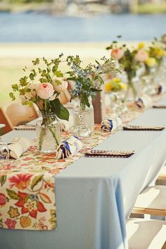 Floral runner on muted blue tablecloth with simple floral arrangements.  Very low budget yet looks amazing.