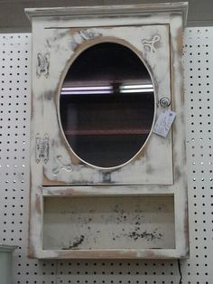 $69 - This wall hanging cabinet has been painted a creamy white and heavily distressed.  It has been wired with a interior light. It measures 18 inches across the front and 6 inches deep. Standing approximately 28 inches tall.  It can be seen in booth D 2 at Main Street Antique Mall 7260 East Main St ( E of Power Rd ) Mesa 85207  480 9241122 open 7 days 10 till 530 Cash or charge accepted