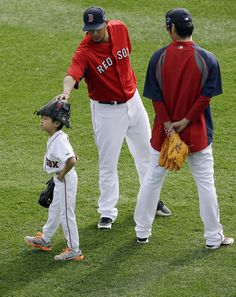 Boston Red Sox relief pitcher Koji Uehara, right, watches as Red Sox pitcher Felix Doubront plays with Uehara's son Kaz, left, during warm-u...