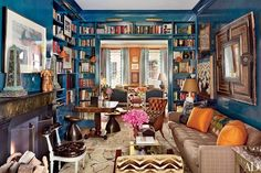 In a Brooklyn brownstone decorated by Nick Olsen, peacock-blue shelving is paired with brass picture lights.