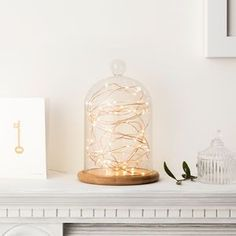 Glass Bell Jar With Copper Micro Fairy Lights   Bring summer evenings in with this luxurious trend. Think dark, elegant colours alongside warm lighting and reflective surfaces. Achieve this look by combining dark velvets with high-gloss furniture and multiple light sources such as fairy lights, lanterns and floor lamps.