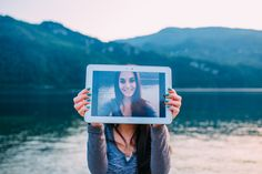 Young woman holds a tablet with a photo of her. Get a Calgary web design for yourself.