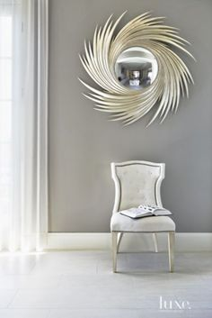 Midcentury-style mirror by Christopher Guy lends drama above a Lillian August chair.