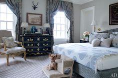 Teddy, a Yorkshire terrier, perches on leopard-spot bed steps in Alex Papachristidis's Bridgehampton bedroom.