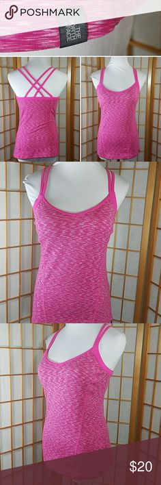 """The North Face, pink strappy back work out tank The North Face pink strappy work out tank with built in shelf bra with light padding. Size small. Measures approx 15"""" across from armpit to armpit when laid flat and is 24"""" long from the top of the shoulder to hem. Light wear on straps and one small mark in middle of back of the shirt shown in photo *please see all photos for condition* in otherwise very good used condition. The North Face Tops Tank Tops"""