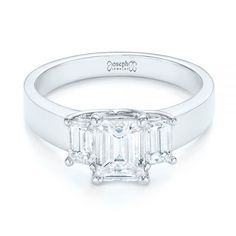 This elegant engagement ring features a large emerald cut diamond in the center of a three-stone setting, with smaller emerald cut diamonds on the sides, and all of these are prong set in white gold. Designed and created by Joseph Jewelry   Seattle, WA   Bellevue, WA   Online   Design Your Own Engagement Ring   #engagementring