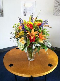 Full and lush, Summer explosion of color.  This arrangement is designed in a wide fluted vase and includes royal sunset lilies, red gerbers, yellow Asiatic lilies, blue hydrangea, blue delphinium, cottage yellow, spray roses, solidago, hypericum berries, millet, high and magic roses and dusty miller.