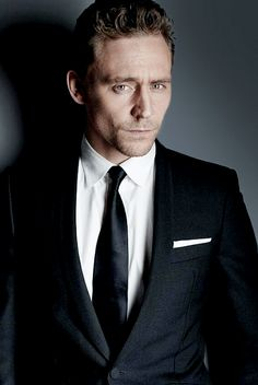 Tom giving you a sexy look while wearing a black suit and matching tie with a white dress shirt too.