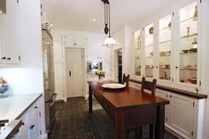 This 1920s farmhouse kitchen keeps lighting simple and minimal, as reminiscent of its history. Made-over with all new furniture and appliances, it's able to keep its historic feel with simple decoration, a small storage table and original floors.