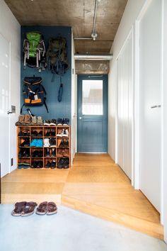 壁にDIYで有孔ボードを張り、バックパックなどを掛けて収納