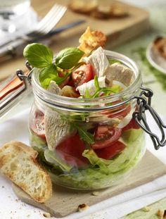 Hähnchen-Schicht-Salat mit Bacon und Ei        Zutaten für 4 Personen: 280 g Hähnchenbrustfilets, 1 Zitrone, Salz und Pfeffer, 1 Lorbeerblatt, 3 schwarze Pfefferkörner, 50 g Frühstücksspeck, 2  Eier,  1 ½  große Tomaten, 1 ½ reife Avocados, 100 g Feta, 3 EL Olivenöl, 1 EL Sherryessig, 1 TL Honig, 1 Kopf Eisbergsalat, 1 Bund Rauke, ½ Bund Basilikum. Zubereitung: 1. Eier kochen. Zitrone heiß abspülen, Schale abreiben und mit ½ l Wasser, Salz, Lorbeer und Pfefferkörnern aufkochen…
