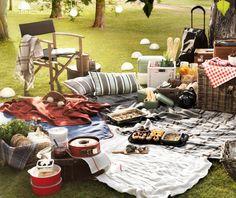 Un picnic con productos textiles, luces, cestos, comida y bebida en un parque con césped y árboles