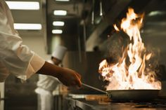 Chef holding flaming pan