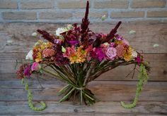 Een boeket in een frame van takken gemaakt en opgevuld met mooie bloemen in herfstkleuren. #school #boeket #frameboeket #bloemen #flowers #bloemschikken #flowerstyling #bouquet #herfst #autumn