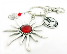 This pretty zodiac keychain features a big and beautiful sun charm that is perfect for a zodiac sign lover. There is a red bead center and a zodiac charm of your choice. . There is a silver swirl charm and a red crystal bead for added color and charm. A unique and pretty keychain