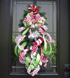 Sock Monkey Christmas Wreath, Christmas Swag, Christmas Wreaths and Swags, Sock Monkey Christmas Decor  Adorable red & white stripe sock monkey in a flourish of ribbon. Cute candy cane & peppermint candy theme. It will be the star of your door this holiday season.  Loaded with ribbon. Red, white, & lime color scheme.  31 Tall 13 Wide & 7 Deep I measure from tip to tip. All the materials used in my floral designs are a wonderful quality. My wreaths can be used outside but they would…