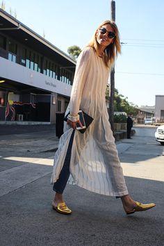 Beauté de la longue tunique blanche, sur le jean, beauté des sandales dorées