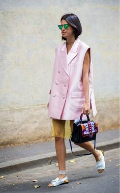 Leandra Medine in a pale pink oversized sleeveless coat over a sheer neon slip, statement purse and slip on shoes